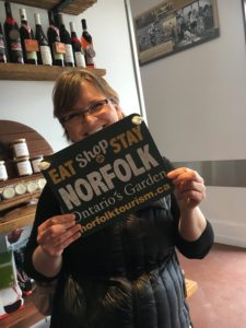 Woman holding sign that says eat, shop, stay Norfolk
